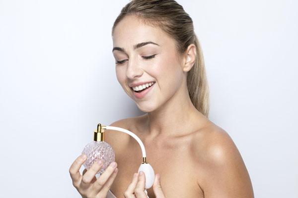 mujer perfumandose con su perfume 24 horas del club del perfume